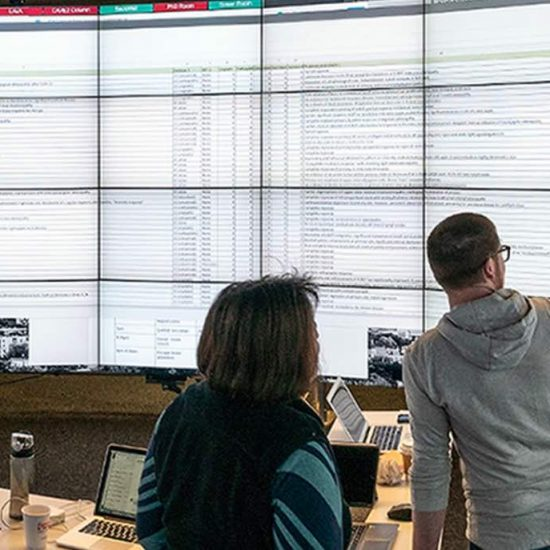 four researchers looking at wall of data